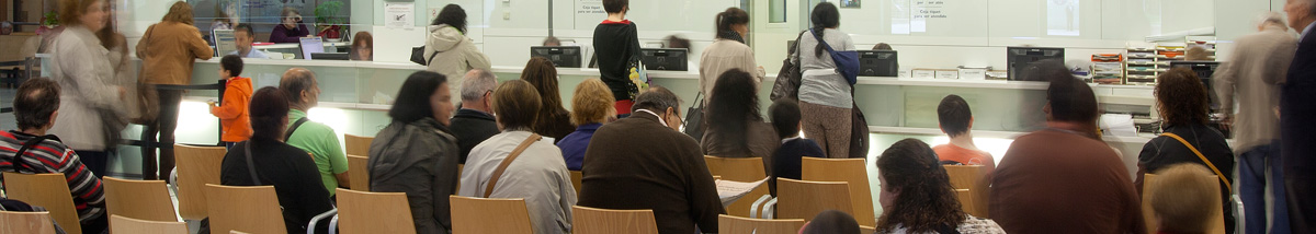 Waiting room at the entrance to the Hospital de Sabadell, with people waiting to be treated