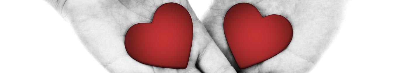 Dos manos compartiendo dos corazones dibujados